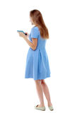 Задний взгляд стоять молодая красивая женщина используя передвижной phon Стоковое фото RF