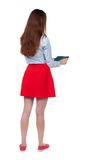 Задний взгляд стоять молодая красивая женщина используя передвижной phon Стоковые Изображения RF