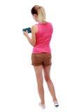 Задний взгляд стоять молодая красивая женщина используя передвижной phon Стоковая Фотография