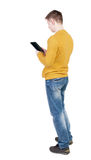 Задний взгляд стоять молодой человек с планшетом в руке Стоковые Фото