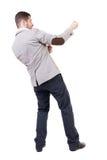 Задний взгляд стоящего человека вытягивая веревочку от верхней части или льнет t Стоковое Фото