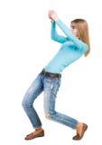 Задний взгляд стоящей девушки вытягивая веревочку от верхней части или льнет Стоковое Фото