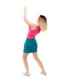 Задний взгляд стоящей девушки вытягивая веревочку от верхней части или льнет Стоковые Изображения RF
