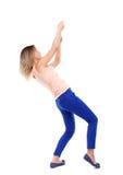 Задний взгляд стоящей девушки вытягивая веревочку от верхней части или льнет к s Стоковая Фотография RF