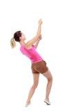 Задний взгляд стоящей девушки вытягивая веревочку от верхней части или льнет Стоковое Изображение RF