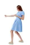 Задний взгляд стоящей девушки вытягивая веревочку от верхней части или льнет Стоковая Фотография