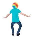 Задний взгляд танцевать молодой красивый человек в парике клоуна Стоковое фото RF