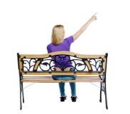 Задний взгляд указывая женщины сидя на стенде Стоковое Изображение