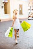 Задний взгляд усмехаясь молодой женщины с хозяйственными сумками Стоковое Фото