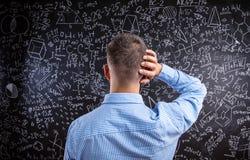 Задний взгляд учителя против большого классн классного с математически sy Стоковая Фотография RF