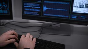 Задний взгляд хакера сидя и делая кибер атака на сети Человек в черных одеждах печатает быстро на пробовать клавиатуры сток-видео