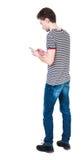 Задний взгляд человека в костюме говоря на мобильном телефоне Стоковые Фото