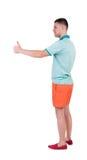 Задний взгляд человека в шортах показывает большие пальцы руки вверх Стоковая Фотография RF