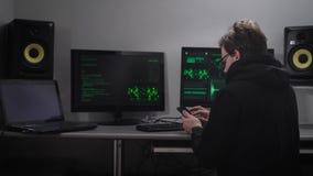 Задний взгляд человека сидя на таблице используя его smartphone Шпионка кибер рубя компьютерную систему с помощью его видеоматериал