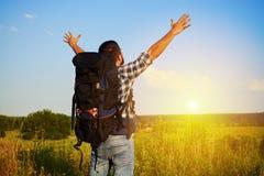 Задний взгляд человека с рюкзаком наслаждаясь красотой солнец поля Стоковые Изображения