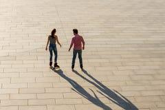 Задний взгляд rollerblading пар Стоковое Фото