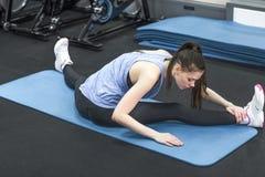 Задний взгляд sporty женщины делая протягивающ тренировку Стоковые Фото