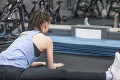 Задний взгляд sporty женщины делая протягивающ тренировку Стоковая Фотография