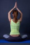 Задний взгляд sporty женщины сидя в положении лотоса над серым цветом Стоковые Изображения