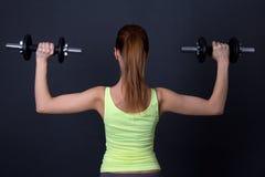 Задний взгляд sporty женщины с гантелями над серым цветом Стоковые Изображения RF