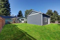 Задний двор заполненный травой с разделенным гаражом Стоковые Изображения