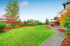 Задний двор с конкретной дорожкой, патио и зеленой травой стоковые изображения