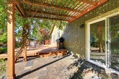 Задний двор с перголой, плиточный пол и деревянный выход украшают Стоковые Фотографии RF