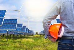 Задний инженер взгляда держа желтый шлем в солнечной станции и ветротурбины производя электричество стоковые изображения rf
