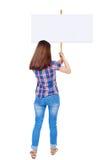 Задняя женщина взгляда показывая доску знака Стоковые Изображения