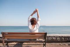 Задняя женщина портрета сидя на стенде на море изумительный взгляд, девушка с вьющиеся волосы, женщина в белой рубашке, отдыхая,  Стоковые Фото