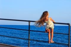 Задняя красивая маленькая предназначенная для подростков девушка с длинным пропуская вьющиеся волосы внутри Стоковое Изображение