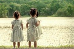 задняя сторона 2 девушек стоя перед рекой Стоковые Изображения