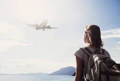 Задняя сторона девушки путешественника смотря самолет летания над морем, перемещением и активной концепцией образа жизни Стоковое Изображение