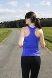 Задняя сторона молодой женщины jogging outdoors Стоковое Фото
