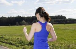 Задняя сторона молодой женщины jogging outdoors Стоковая Фотография