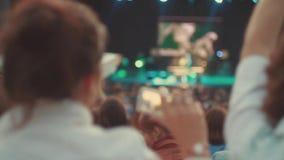 Задняя сторона танцев женщины на концерте в реальном маштабе времени лета среди другого Всход на телефоне Диапазон выполняет на э сток-видео