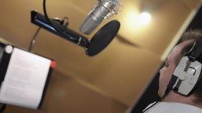 Задняя сторона человека эмоционально поет в наушниках перед микрофоном студия видеоматериал