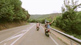 Задняя сторона людей в шлемах едет на самокатах на дороге горы зеленые валы перемещать Путешествие сток-видео