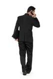 Задняя съемка идя бизнесмена, беседы на телефоне Стоковая Фотография RF