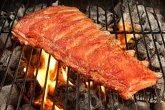 Задняя часть или Spareribs младенца свинины на гриле BBQ с пламенами Стоковые Фотографии RF