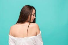 Задняя часть молодой женщины представляя на сини Стоковое Изображение