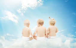Задняя часть младенца в пеленках сидя на облаках над предпосылкой неба Стоковое Фото