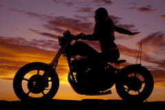 Задняя часть руки езды мотоцикла женщины силуэта стоковые фото