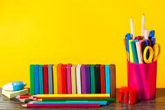 задняя школа принципиальной схемы к Школьные принадлежности на пастельной предпосылке Стоковое Фото