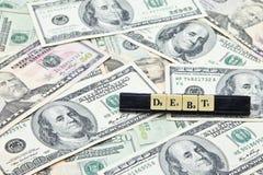 Задолженность слова на куче банкнот доллара США Стоковые Фотографии RF