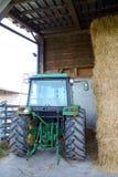Зад трактора припаркованный поруками сена стоковые фото