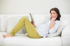 Задумчивая беременная коричневая с волосами женщина читая газету Стоковое Изображение