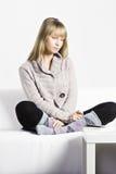 Задумчивая белокурая женщина на софе стоковые изображения rf