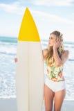 Задумчивая белокурая модель в купальнике держа surfboard Стоковая Фотография RF