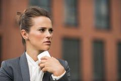 Задумчивая бизнес-леди около smartphone офисного здания говоря стоковые фотографии rf